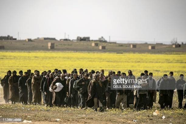 Men suspected of being Islamic State group fighters walk together towards a screening point for new arrivals run by USbacked Syrian Democratic Forces...