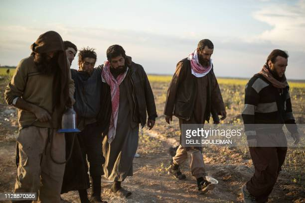 TOPSHOT Men suspected of being Islamic State group fighters walk together towards a screening point for new arrivals run by USbacked Syrian...