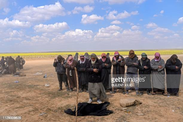 Men suspected of being Islamic State group's members pray at a screening area held by the USbacked Kurdishled Syrian Democratic Forces after they...
