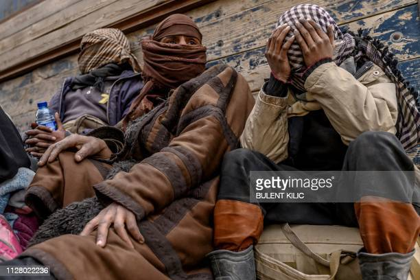 Men suspected of being Islamic State wait to be searched by members of the Kurdish-led Syrian Democratic Forces after leaving the IS group's last...
