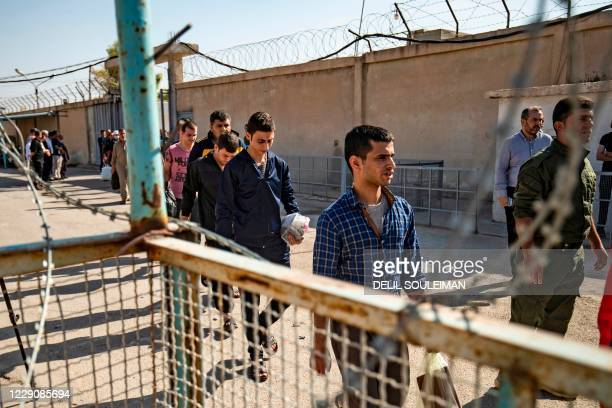 Men suspected of having collaborated with the Islamic State group, leave the Kurdish-run Alaya prison in the northeastern Syrian city of Qamishli,...