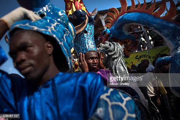 Men take a break from their hot festival masks during carnival weekend on February 27 2011 in Jacmel Haiti This year's celebration was met with mixed...