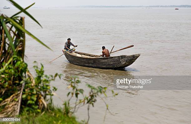 Men take a small rowboat on the Pusur River on April 12 2016 in Mongla Bangladesh