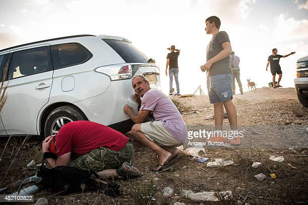 Men take cover behind a car due to a rocket attack siren going off while watching Israeli attacks inside Gaza from the top of a hill on the sixth day...