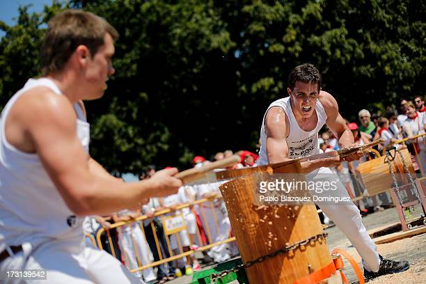 Men take part in a Basque Country sports competition on cutting wood during the third day of the San Fermin Running Of The Bulls festival on July 8...