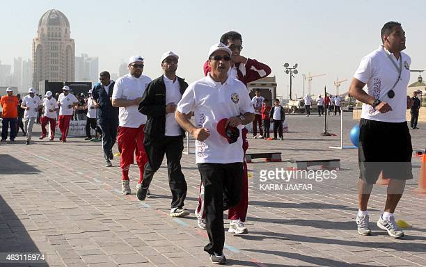 Men take part in a group run during the Qatar National Sport Day in the capital Doha on February 10 2015 More than a million Qataris were given a day...