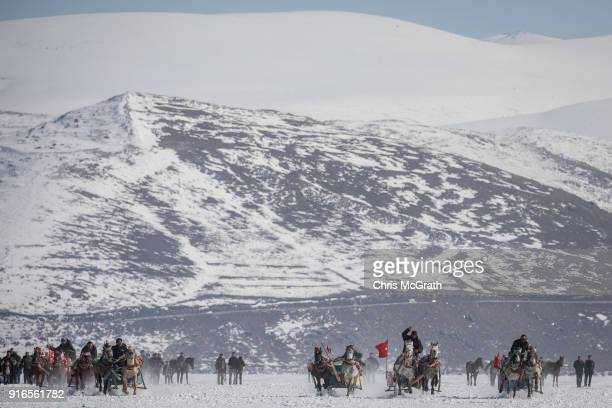 Men take part in a horsedrawn sled race across the frozen Cildir Lake during the yearly Golden Horse festival on February 10 2018 in Cildir TurkeyThe...