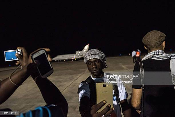 Men take photos as the plane of ExPresident Yahyah Jammeh sits on the tarmac prior to leaving the country on January 21 2017 at Banjul International...