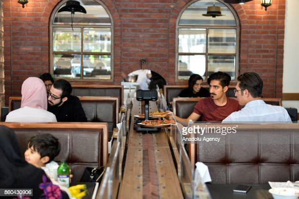 Men take their food served by robot waiter which moves on rail system placed between tables at the first robotic restaurant 'RoboChef' in Tehran Iran...