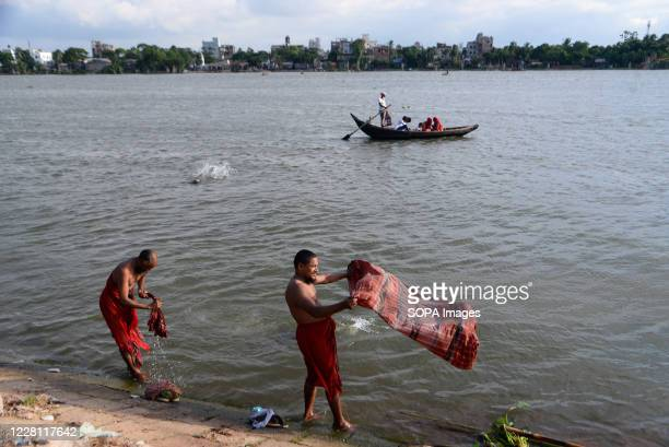 Men taking a bath at the Buriganga River. Dhaka is getting back to its normal life after some months of the ongoing pandemic.