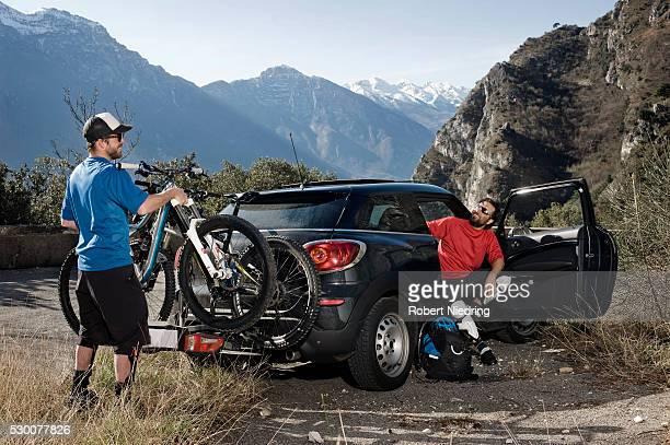 Men taking mountainbikes off car, Italy