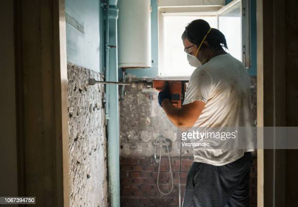 men taking off old tile from wall with jackhammer - demolishing stock pictures, royalty-free photos & images
