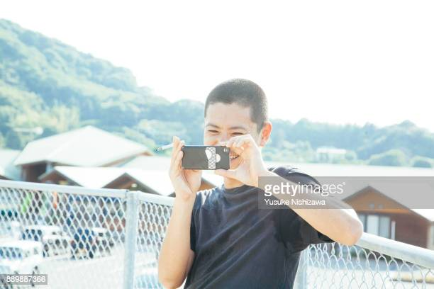 men taking pictures with smartphones - yusuke nishizawa stock pictures, royalty-free photos & images