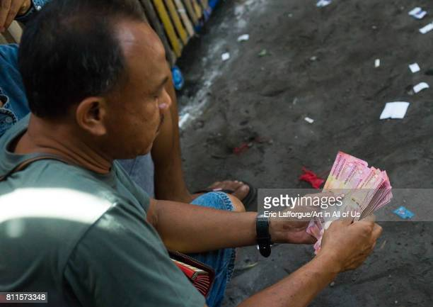 Men taking the money for the bets during a cockfigting event Bali island Canggu Indonesia on July 18 2015 in Canggu Indonesia