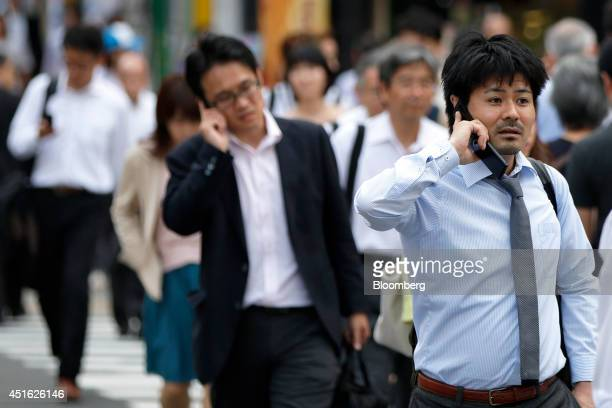 Men talk on their mobile phones while crossing a street in Tokyo Japan on Monday June 30 2014 Competition for new subscribers in Japan is...