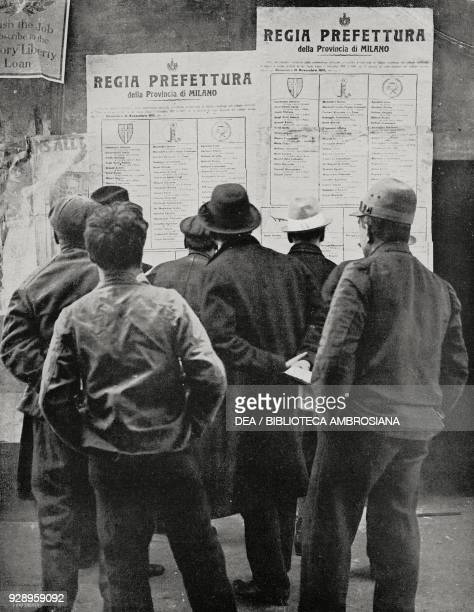 Men think in front of the electoral posters during the electoral campaign in Milan Italy from the magazine L'Illustrazione Italiana year XLVI no 46...