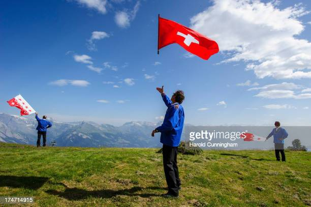 Men throw a Swiss and canton of Valais flags on July 28 2013 in Nendaz Switzerland About 150 Alphorn blowers performed together on the last day of...