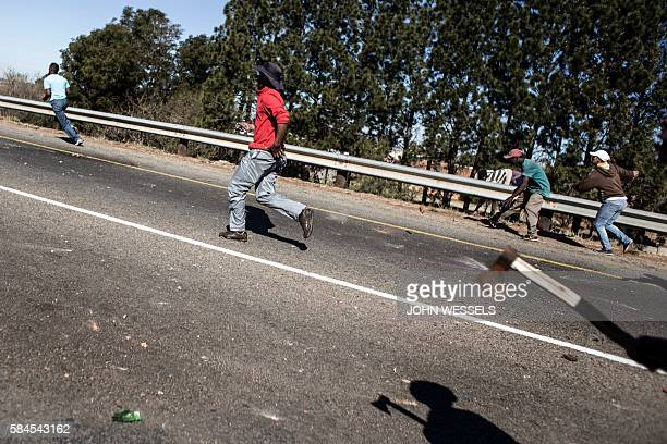 Men throw rocks and run after a service delivery protest turned violent between two communities clashing over a suspected electricity theft on July...