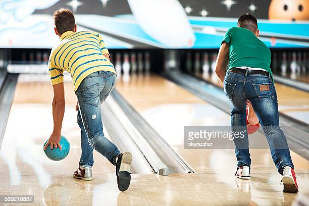 Men throwing a bowling ball.