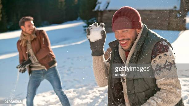 men throwing snowball into air - brown glove stock pictures, royalty-free photos & images