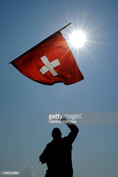 A men throws a Swiss flag during the opening day of the Federal Alpine Wrestling Festival on August 21 2010 in Frauenfeld east of Switzerland More...