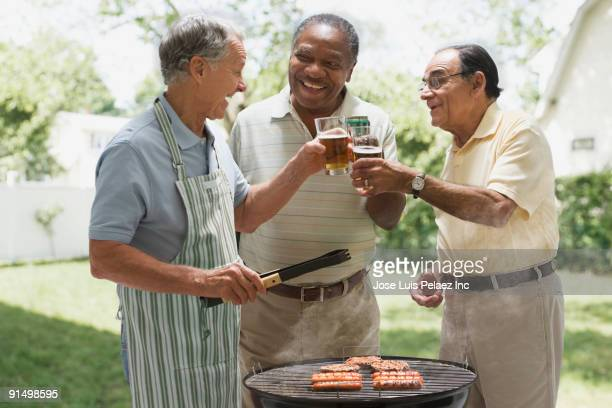 Men toasting beers over backyard barbecue grill