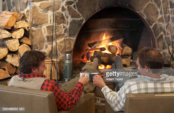 Men toasting in front of log fire, rear view