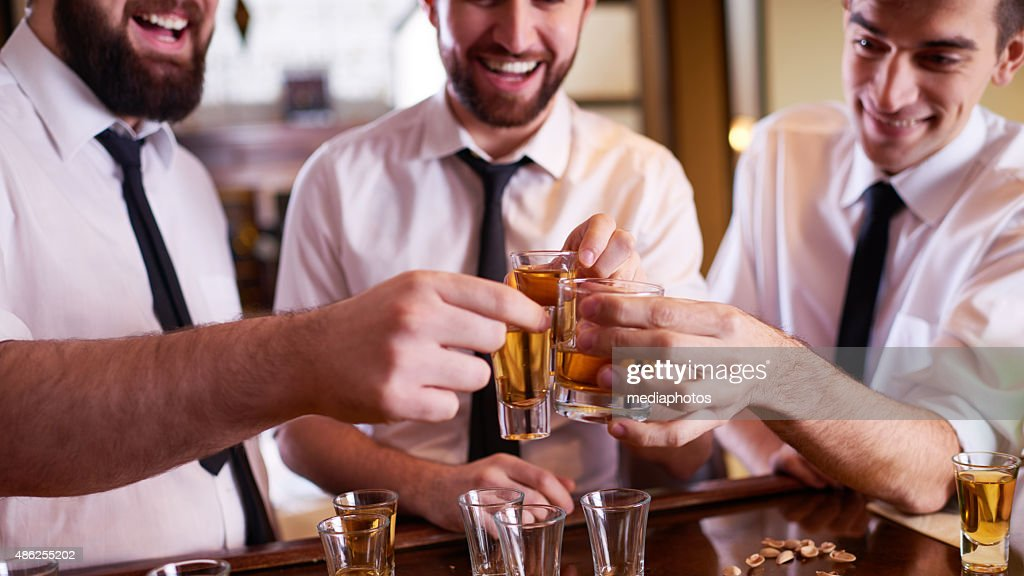 Men toasting in the bar : Stock Photo