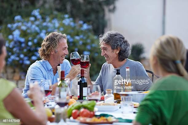 2 men toasting in wineglasses at dinner