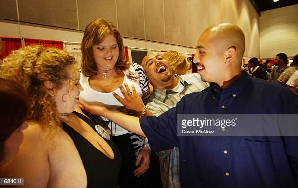 Men touch the breasts of TopHeavycom model Kitty as comodel KountryGirl looks on at the Erotica LA 2002 adult industry tradeshow on June 7 2002 in...