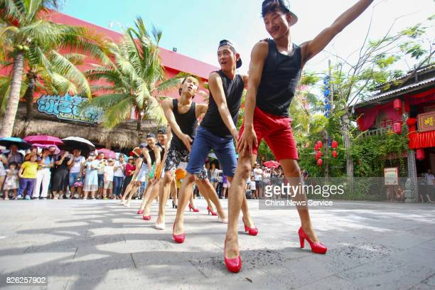Men tourists wearing highheeled shoes perform bamboo pole dancing during an activity on August 3 2017 in Sanya Hainan Province of China A scenic spot...