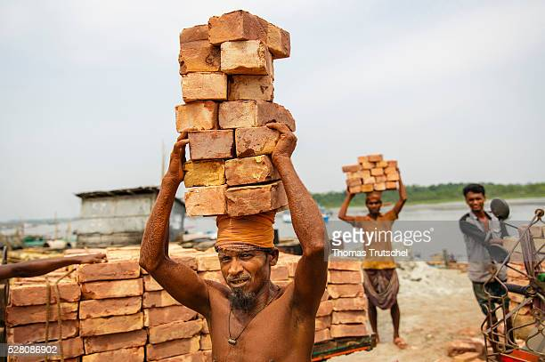 Men transport bricks on their heads on the harbour of Mongla on April 12 2016 in Mongla Bangladesh