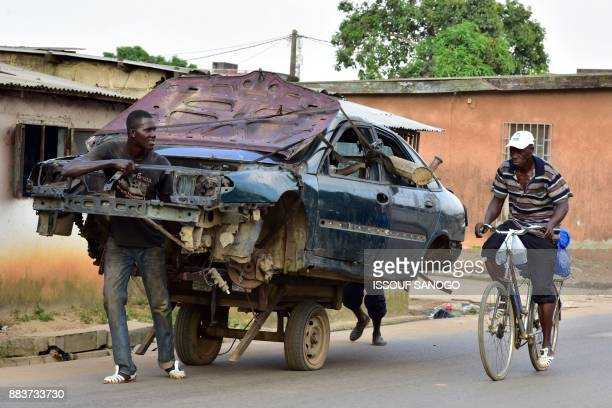 Men transport the carcass of a car as a cyclist drives past in a neighborhood in Abobo a suburb of Abidjan on December 1 2017 / AFP PHOTO / ISSOUF...
