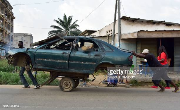 Men transport the carcass of a car on a twowheeled carriage in a neighborhood in Abobo a suburb of Abidjan on December 1 2017 / AFP PHOTO / ISSOUF...
