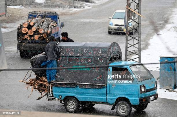 Men transport wood fire on their vehicles through a street as it snows in Skardu on January 23, 2021.