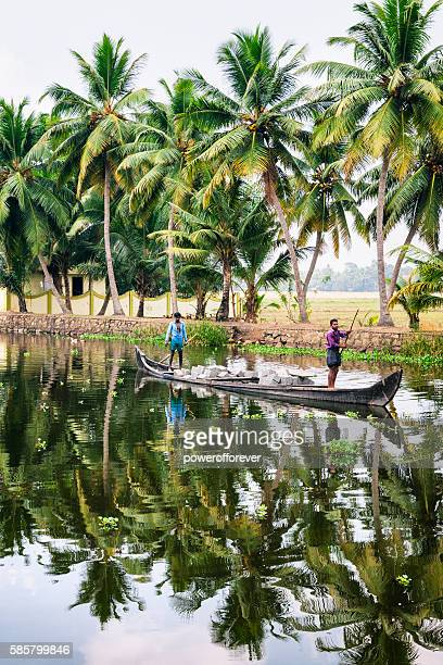 Men transporting bricks by Kettuvallam on the Kerala Backwaters, India
