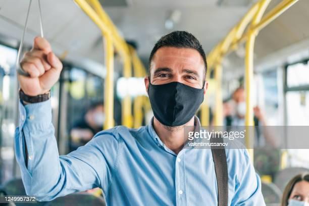 uomini che viaggiano sull'autobus sorridendo dietro la maschera, durante covid-19. andrà tutto bene - autobus foto e immagini stock