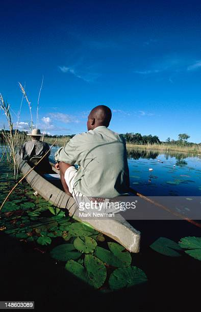 men travelling through wetland in traditional mokoro (dugout canoe). - men stockfoto's en -beelden