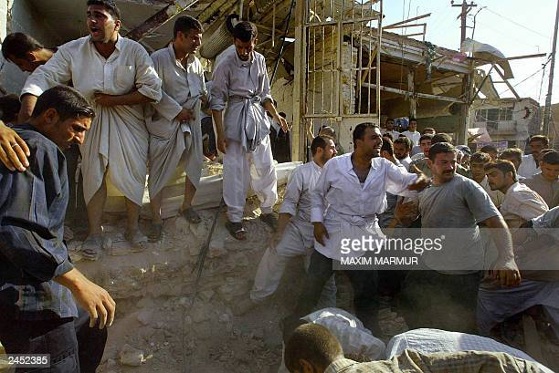 Men try to clear the blast site 29 August near the Shrine of Imam Ali one of Shiite Islam's holiest shrines in the central city of Najaf 180 km south...