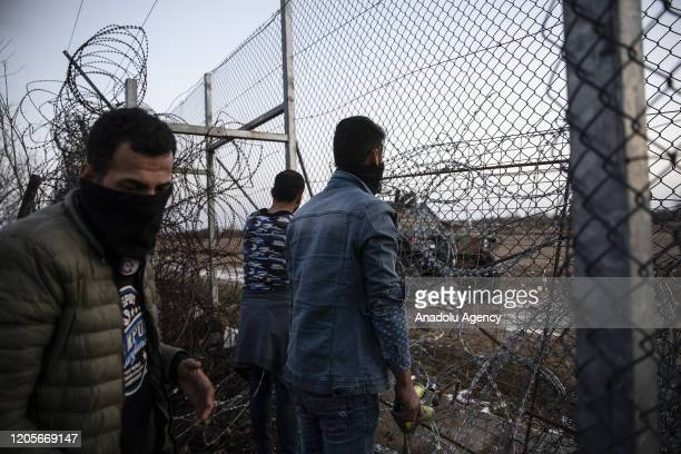 Men try to open border fence as Greek security forces use tear gas and water cannon to disperse asylum seekers in the region between the Kastanies...