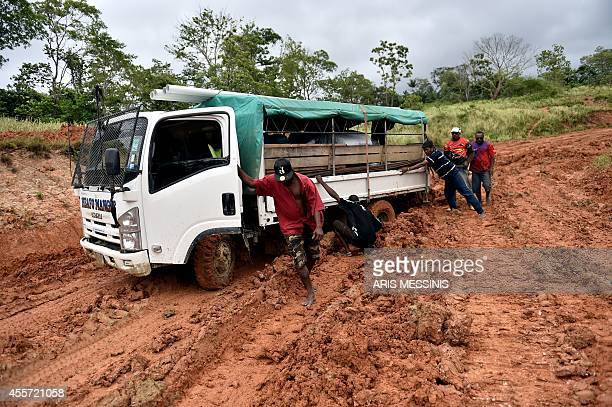 Men try to push a truck stuck in the mud on a road in the jungle of Papua New Guinea on September 4 2014 AFP PHOTO / ARIS MESSINIS