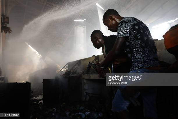 Men try to salvage items as firefighters work to put out a blaze at PortauPrince's historic Iron Market on February 13 2018 in PortauPrince Haiti...