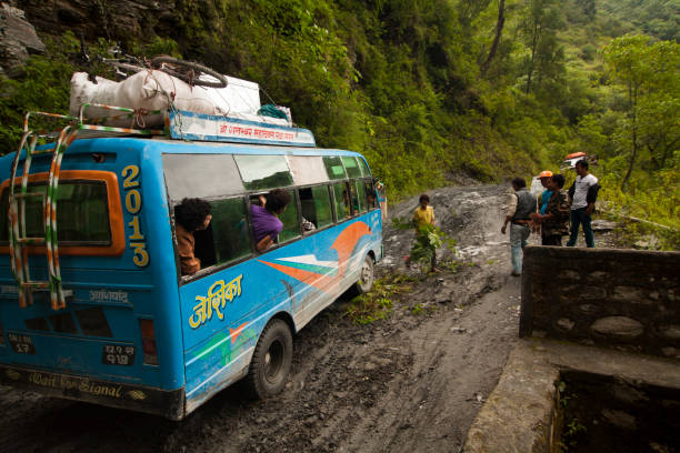 Men trying to free a bogged bus on the Beni Jomsom Sadak dirt road which runs along the Kali Gandaki River in a densely forested area on the road from Beni to Jomsom, Nepal.