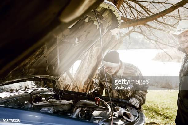 Mannen proberen te beginnen met auto met acculader