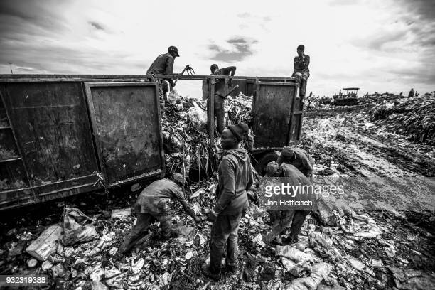 Men unload a truck at the Dandora rubbish dump on March 14 2018 in Nairobi Kenya The Dandora landfield is located 8 Kilometer east of the city center...
