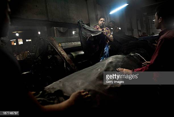 Men unload leather hides from a machine in a tannery the Phoenix Leather Complex November 10 2013 in the Hazaribagh neighborhood of Dhaka Bangladesh...