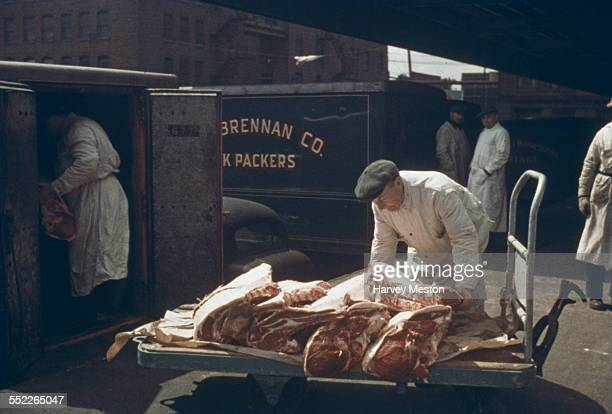 Men unload meat from vans at a meat packing plant in Chicago USA circa 1955
