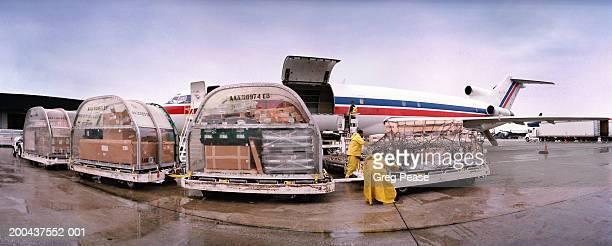 Men unloading cargo plane in rain, sunset