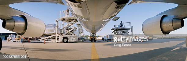 Men unloading cargo plane, sunset, low angle view (wide angle)