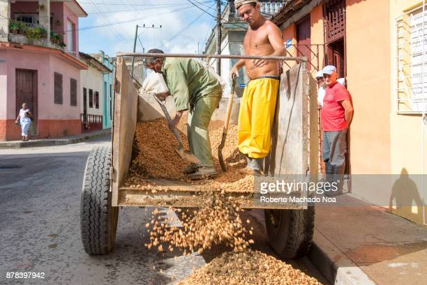 Men unloading construction gravel on the front of a private house After economic changes many have started to reconstruct their houses